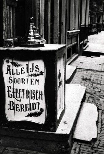Consumptieijs. Op een stoep in een straat staat een ijskist met stolpdeksel, op de zijkant de tekst