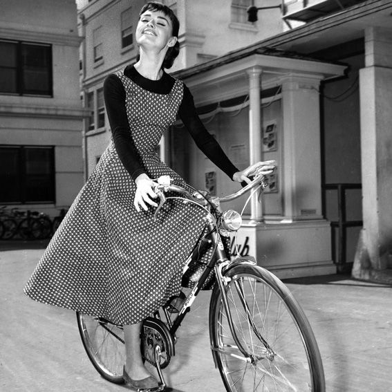 Through the Ages: Beauties on Bikes - Audrey Hepburn: On the set of her film Sabrina in 1954, Hepburn wheeled around in a printed A-line dress worn over a black long-sleeved tee and paired with ballet flats. #InStyle