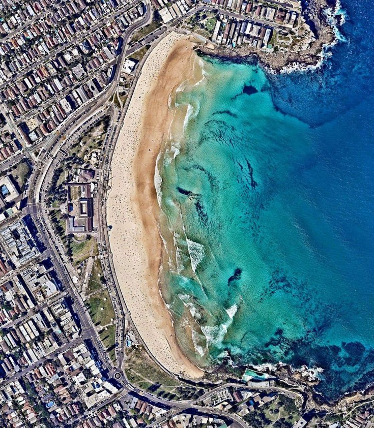 """Bondi Beach and its surrounding suburb are located in Sydney, Australia. One of the city's most stunning and popular destinations, the beach gets its name from the Aboriginal word """"Bondi"""" that means waves breaking over rocks.  Instagram: http://bit.ly/2FuVjaz  33°53′28″S 151°16′40″E  Source imagery: Nearmap"""