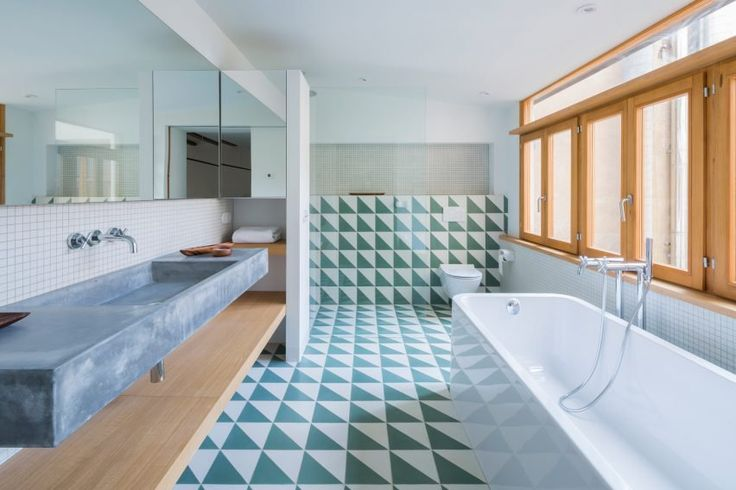 Colourful restored tile flooring and wooden ceiling beams add character to this Barcelona apartment refurbished by local studio Nook Architects.