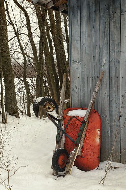 Old wheelbarrow leaning against barn by Sandralise | Stocksy United