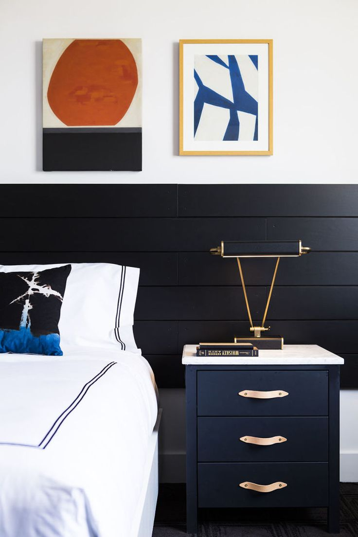 This black and white bedroom with a rich dark blue nightstand and graphic art is all about a moody palette and urban-chic touches.