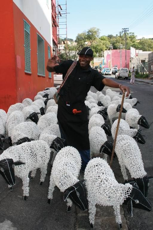 """Shepherd"" Godza Mtizwa from Streetwires was spotted herding 200 life-sized beaded sheep through the streets of Cape Town."