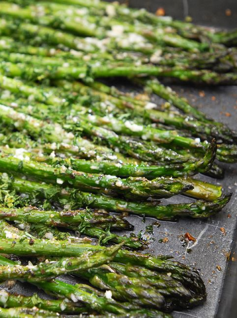 Cut wooden ends off asparagus and place in a baking dish to create one layer. Pour on olive oil, and lemon juice. Toss to coat and rearrange into one even layer. Sprinkle on garlic. Dust with Romano, parsley, black pepper and salt. Roast in oven at 400 degrees until done, about 15 minutes