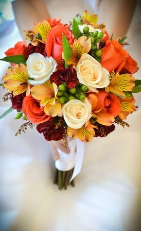 Ivory and orange roses, burgundy mini carnations, orange alstroemeria and green hypericum berries.