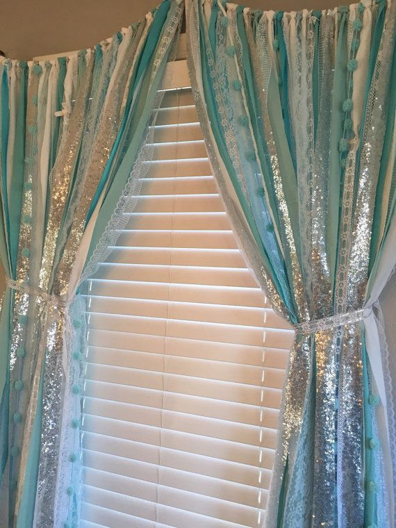 Perfect for any Frozen theme room, party or event. The Frozen inspired Garland curtain is made with a blend of icey blues and squad along with sparkley silver sequin and lace.  Torn and rag tied -