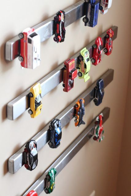 cute way to store toy cars so kids can put them away themselves and easily see them too - magnetic knife rack from Ikea or Amazon and thin magnets (might minis?) superglued to bottom of cars - cute!