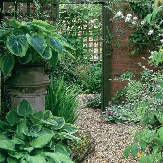 Mirrors and trelliswork Trelliswork is reflected in a tall mirror, creating the illusion of a distant view and elongating the plot. Hostas flourish in and around the chimney.