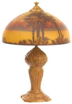 an early table lamp possilby phoenix lamp company reverse painted shade with palm trees in front of lake with sun setting behind mountains