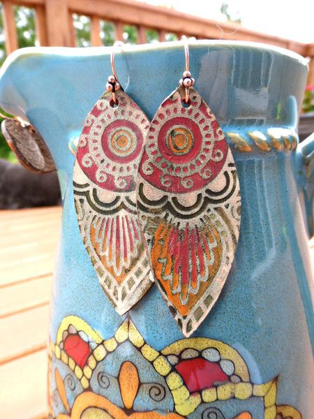 These earrings are lightweight measuring 2 1/2 inches long, 1 inch wide, thin and are lightweight. Hand painted these earrings are made with embossed leather and to me are the perfect earthy designs f