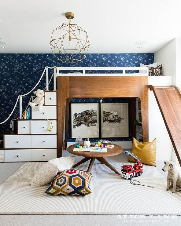 Charming contemporary blue and white boy's bedroom is furnished with a modern two tone loft bed fixed against a wall covered in Hibou Home Boy's Wallpaper Pirate Blue and finished with storage stairs, a white rope railing, and a slide.