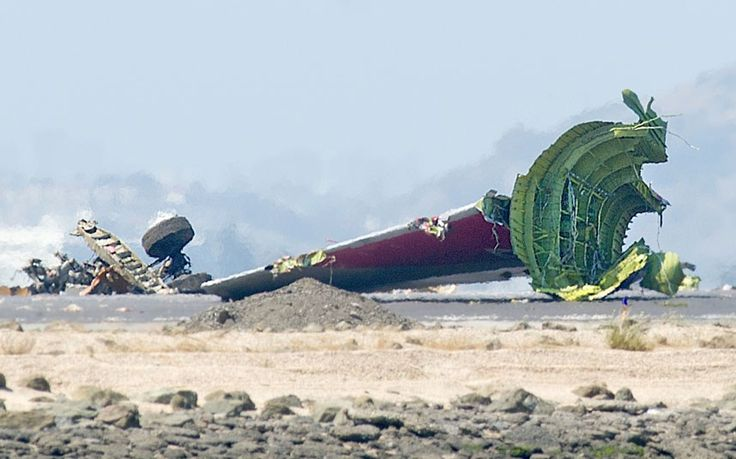 The detached tail and landing gear of Asiana Flight 214 rest on the tarmac after the plane crashed at San Francisco International Airport