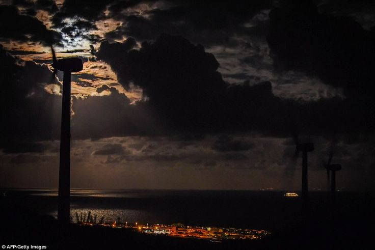 A wind turbine spins backdropped by a supermoon, El Poris de Abona on the Spanish Canary I...