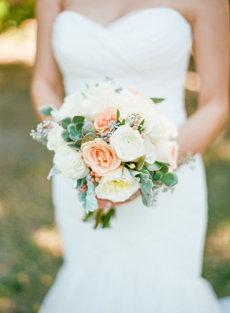 The bride's bouquet featured roses, ranunculuses, berries, and greenery. | Photo: Daniel Kim Photography, Floral Designer: Phoenix Flower Shops