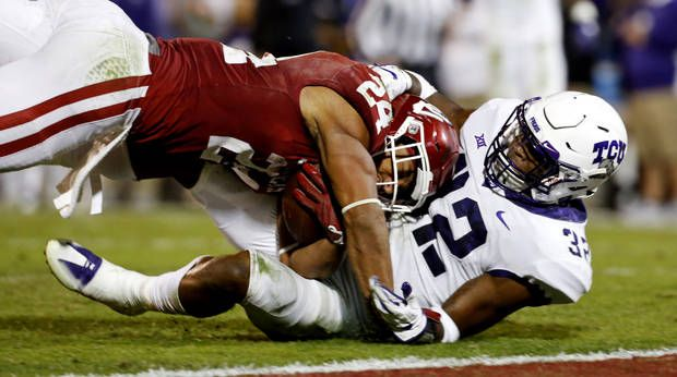 Oklahoma's Rodney Anderson (24) scores on a pass reception at the close of the first half during a college football game between the University of Oklahoma Sooners (OU) and the TCU Horned Frogs at Gaylord Family-Oklahoma Memorial Stadium in Norman, Okla., on Saturday, Nov. 11, 2017. TCU's Travin Howard (32) is defending. Photo by Steve Sisney, The Oklahoman