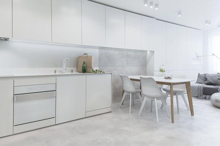 White appliances by Karim Rashid for Gorenje pair with concrete floors in the apartment's kitchen.