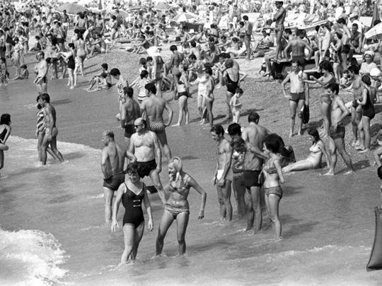 Italiani in vacanza a Ferragosto si rilassano in riva al mare. Liguria, 15 agosto 1969.
