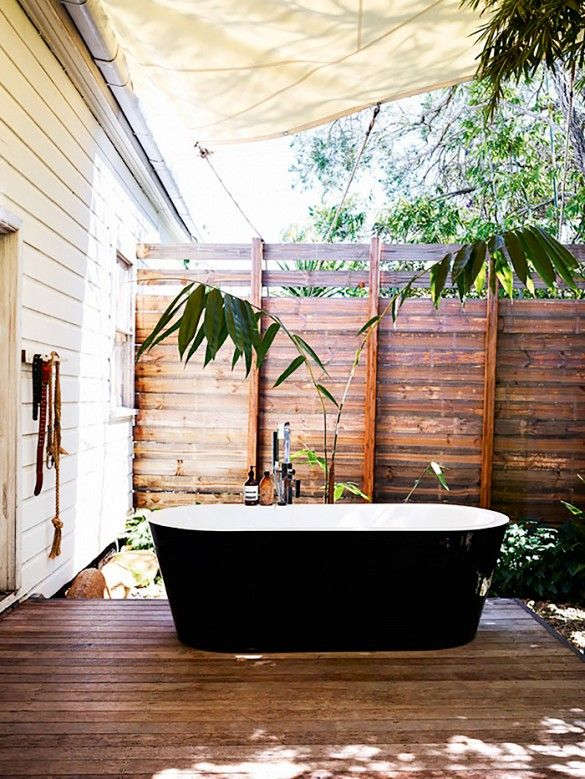 Australian artist David Bromley set a contemporary black freestanding bathtub on his back porch. Beneath an awning and surrounded by trees, it gets a bit of sun and shade.