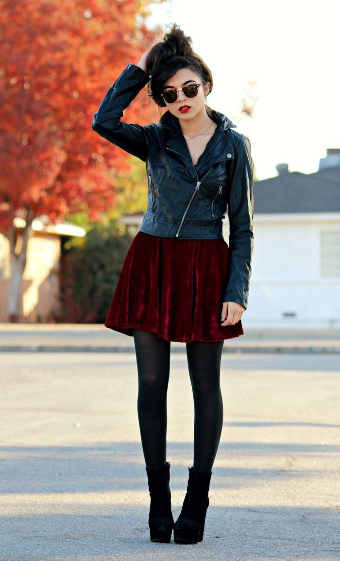 Leather biker jacket zipped up over dolly mini dress, black tights, chunky heels and sunglasses.