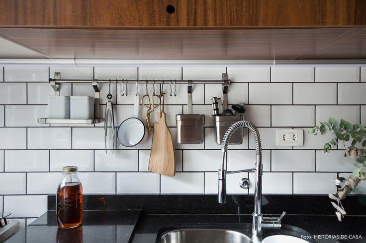 Cozinha tem armários de madeira, subway tiles com rejunte escuro e bancada de granito preto.