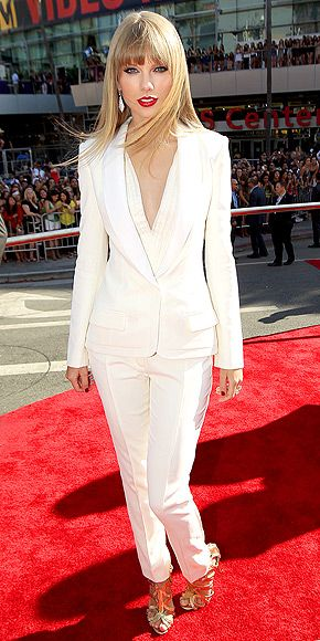 Taylor Swift in a sleek white J. Mendel pantsuit, dramatic dazzling Ofira earrings and a Lorraine Schwartz ring, plus classic red lips.