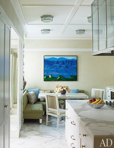 In the kitchen, Greek Key chairs by Jonas are pulled up to a table with a base by Craig Van Den Brulle; the ceiling lights are by Ralph Lauren Home.