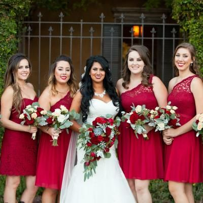Bridesmaids in red lace dresses with one shoulder strap and white and red bouquets   David De Dios Photography   villasiena.cc