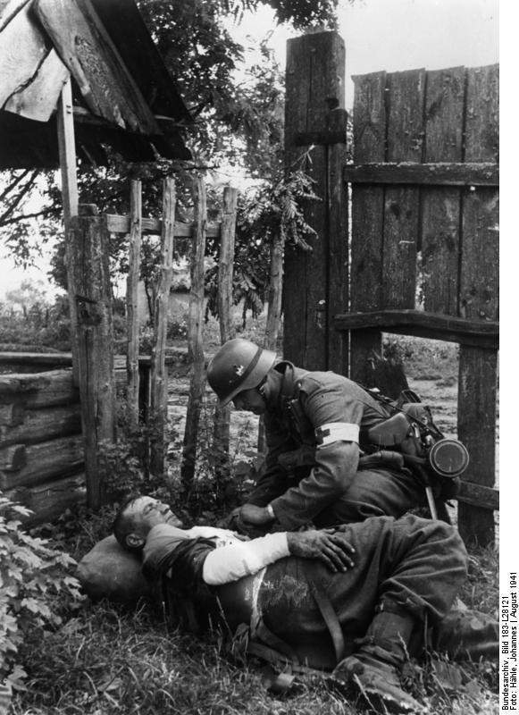German medic patches up a wounded comrade somewhere in the Ukraine, August 1941. The German military ambulance service came under extreme pressure in Russia as the evacuation of the wounded was suddenly a major joint operation involving both land and air assets. German efficiency wasn't enough.