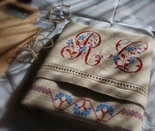 ricamo a punto croce  su canapa tessuta a mano (Cooperativa Lo Dzeut - Champorcher). Filato DMC blu 825 e rosso 815. Lettere con fiordalisi estratte dall'alfabeto Rouyer n. 144