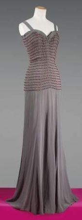 SCHIAPARELLI, haute couture, No. 73461, Summer 1940 Dress long evening in mouse gray crepe  top neckline ruffle edge on straps bust to small hips quilts effect fintion smocking accented with faceted ruby beads, fluid skirt worked in bias. White claw, black graphics. Estimate: 3000 / € 4000