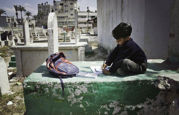 Mahmoud Jilu, 4 ans, est né dans le cimetière d'Al-Sheik Shaban à #Gaza. Son père cumule deux emplois mais n'a pas eu d'autre choix que d'installer sa femme et ses quatre enfants dans une maisonnette au milieu des tombes. Après l'école, Mahmoud joue au ballon dans la cour du cimetière et fait ses devoirs sur le tombeau d'un membre de sa famille.     www.emanmohammed.com #EmanMohammed  #photo #photographie #photographer #photography #photographe #OlivierOrtion #photojournalist…