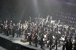 Orquestra – Wikipédia, a enciclopédia livre  designa não só um grupo de músicos que interpretam obras musicais com diversos instrumentos como também uma parte física do teatro grego, que se caracterizava por um coro formado por bailarinos e músicos que faziam evoluções sobre um estrado chamado orkhéstra (ορχήστρα)
