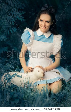 Girl Costumed as Alice in Wonderland with The White Rabbit - Portrait of a smiling girl in a blue costume holding a white bunny