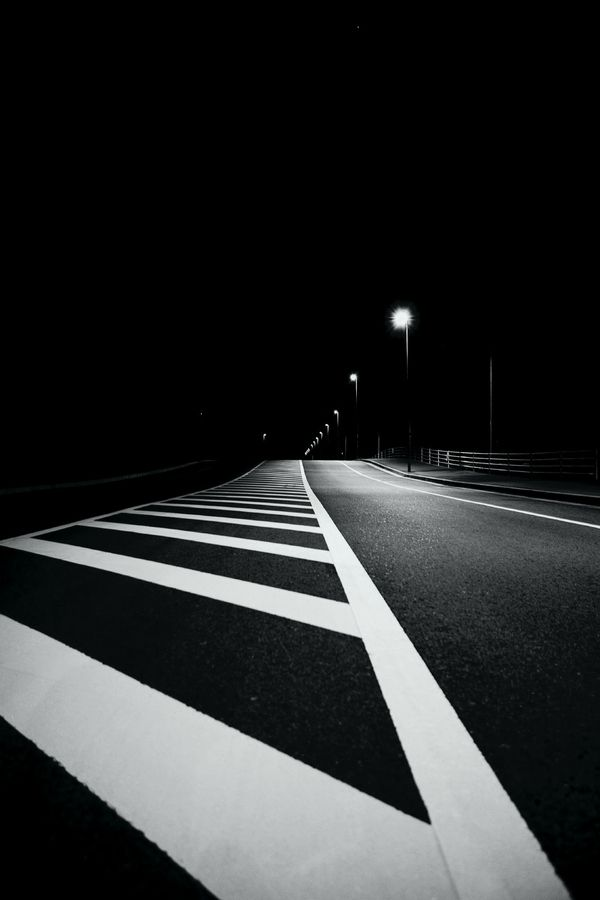 this photo has contrast because the solid lines on the road stand out greater than the rest of the road because its so dark.