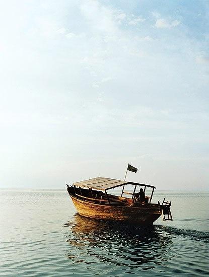 A dhow cruises Lake Tanganyika at dusk.
