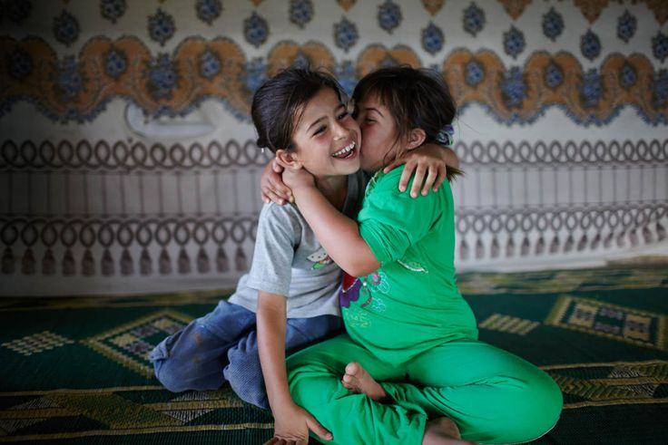 Aya, left, is kissed by her handicapped sister, Labiba, 11, in their family's home in an informal settlement in Dalhamiyeh in the Bekaa Valley, Lebanon, Tuesday, July 30, 2013. 'She's a trouble maker - if somebody hits her she hits him back, she's tough, she's witty, she's curious', says her older sister Houdoud talking about Aya.