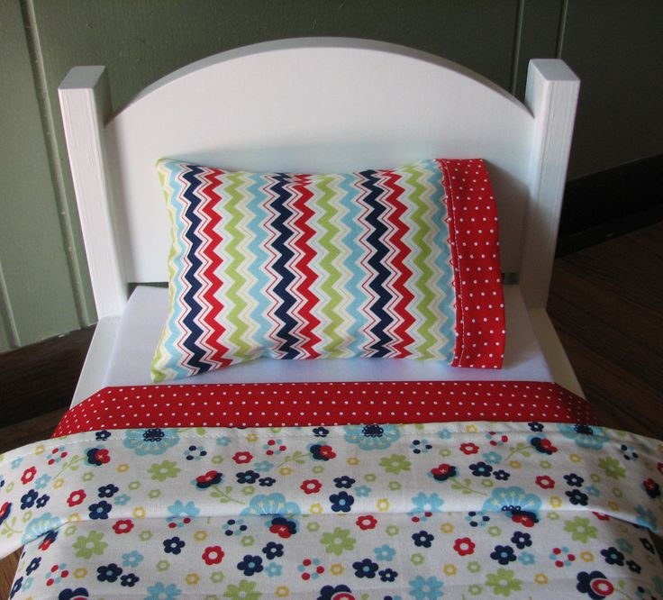 Made from Riley Blakes Dress Up Days fabric this reversible blanket set is beautiful in its simplicity. Light blue, dark blue and red flowers decorate the top of the blanket which is backed with a red and white polka dot fabric. The pillowcase is made in a coordinating chevron with a red polka dot accent. (*Bed and mattress sold separately)  Red / Blue Flower Bedding Set includes:  **Measurements are approximate**  Reversible Blanket - 17 x 21 Pillow - 6 x 4 Pillowcase - 7 1/2 x 5 To view…