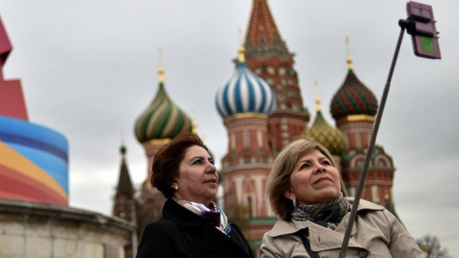 Russians who use selfie sticks to take photographs
