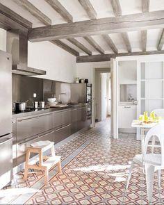 Les poutres du plafond peintes d'un gris lasuré qui s'harmonisent avec les éléments de la cuisine et apportent de la clarté.
