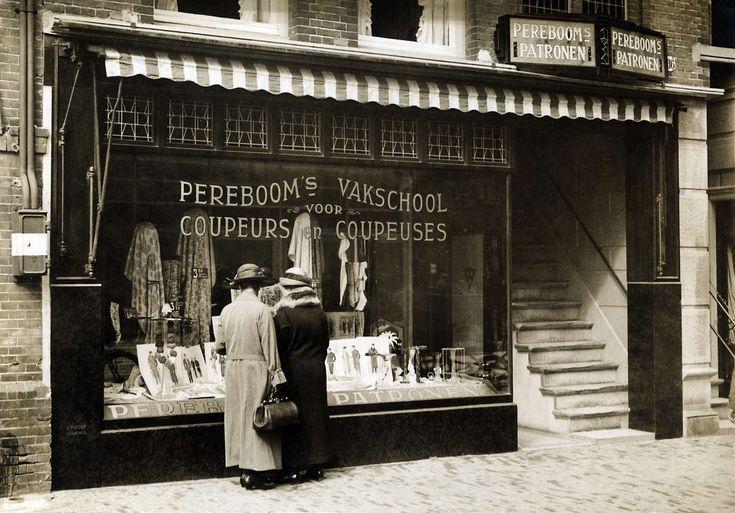 """1924.Een winkel van knippatronen.Twee dames bekijken de etalage met stoffen en knippatronen. Op de ruit staat: """"Peereboom's vakschool voor Coupeurs en coupeuses"""".[Amsterdam], Nederland,"""