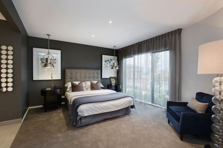 This classic but contemporary master bedroom reflects a mid tone palette of stone and greys, with highlighted details of chrome and glass lights and features button detail bed frame. As displayed in Dunedin 28 at Saltwater Coast Estate.