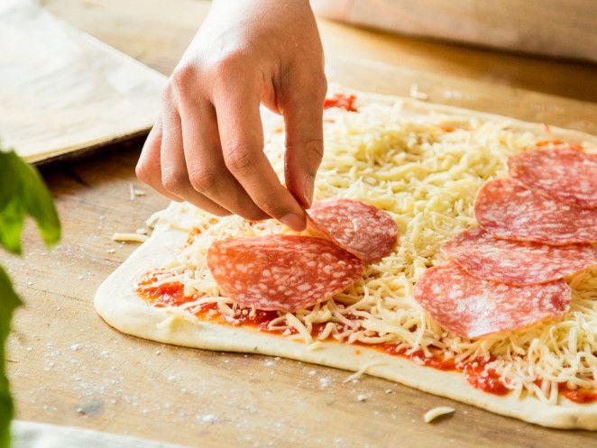 Salami auf Pizza verteilen