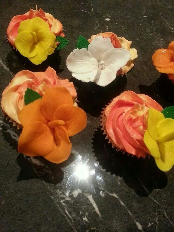 White Chocolate Mud cupcakes with yellow and orange buttercream frosting topped with a handmade frangipani
