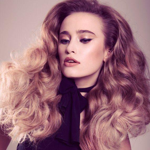 Большие кудри в классическом стиле — очень модные в 2014 году. Используйте щипцы для завивки вместо бигудей, чтобы концы оставались более прямыми. Расчешите волосы и разделите волны, закрепив их лаком для волос. 2014г.