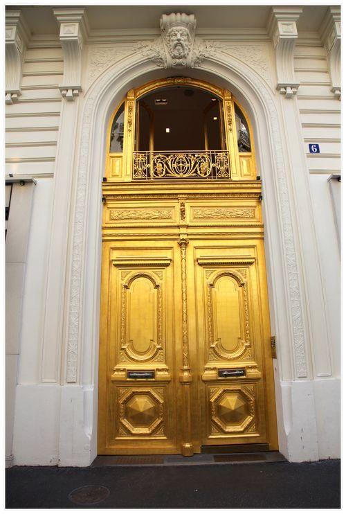 A golden door in a residential building in Paris