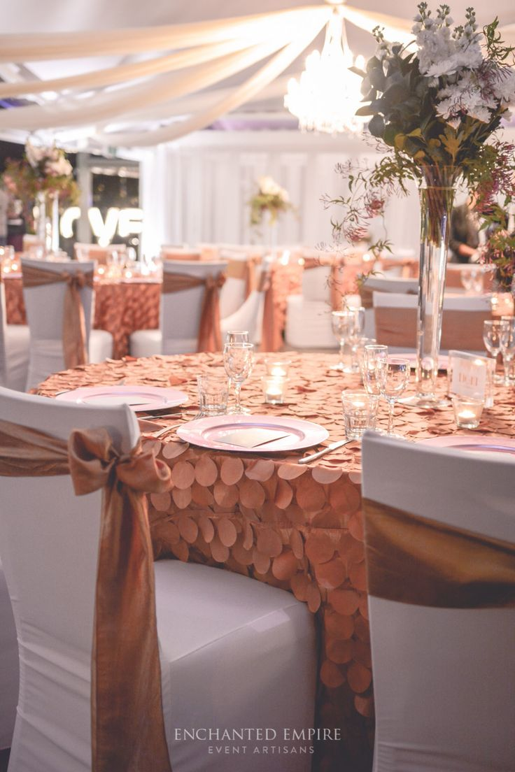 This clean, elegant wedding theme was all about romance. Exquisite gold Peacock Tablecloths exuded texture and opulence. Glass tealight votives provided a gorgeous ambiance for beautiful florals, created by Stem Design. Each place setting had Blush Pink Charger Plates with custom golden menus and table numbers. The ivory draping and chandelier finished the room perfectly, illuminating it and adding a sense of extravagance…