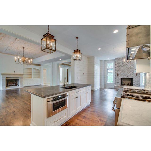 White Kitchen Open Concept white shiplap, brick fireplace, open concept, and lantern lighting