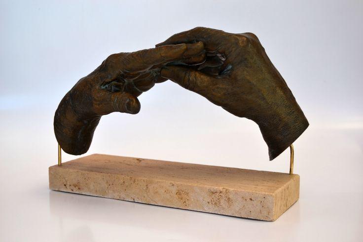 Las manos de los padres de Montse poniéndose el anillo de compromiso como regalo en su 50 Aniversario, realizadas en producto cerámico acabado en bronce antiguo sobre peana de mármol travertino.