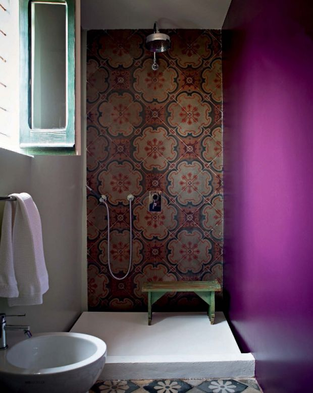 Standing shower with magnificent tile and fuschia painted wall. Love the green stool and open window.