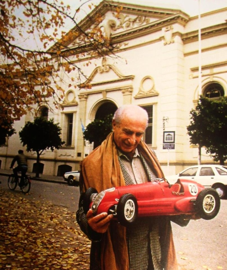 What a lovely photo of Manuel Fangio with a scale model of his 1950s F1 Mercedes.